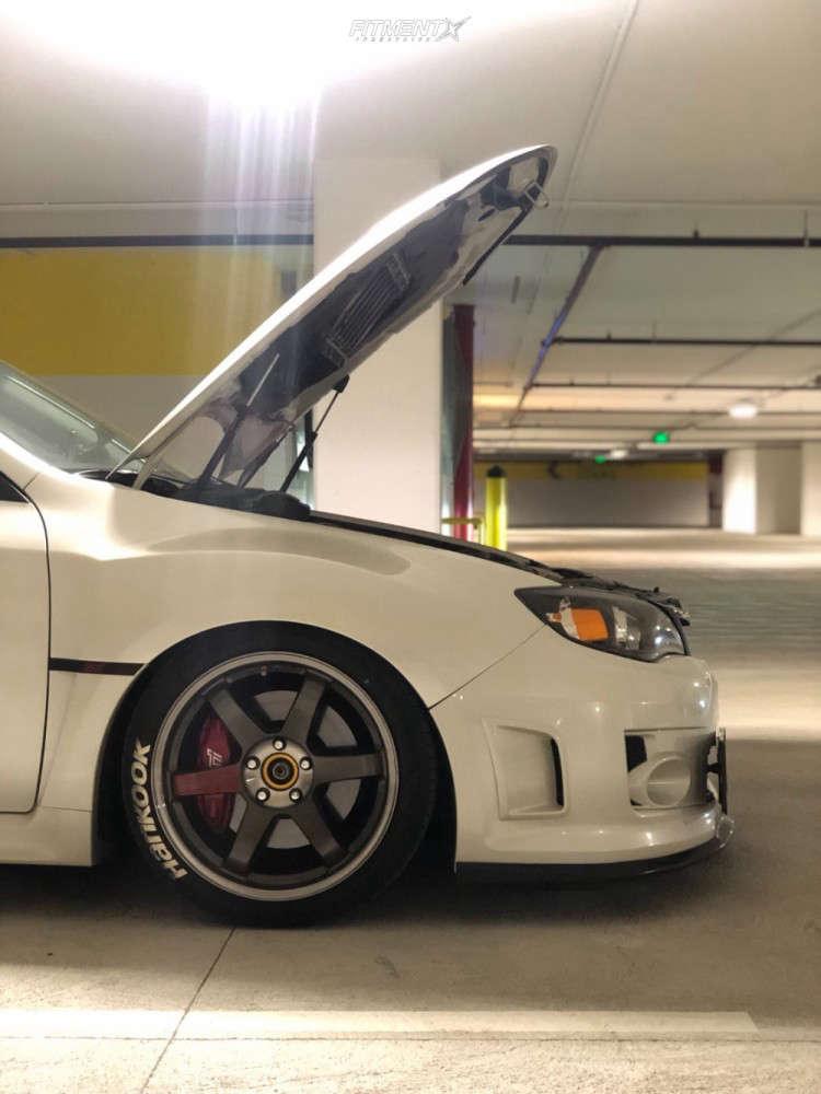 A dude sitting on the rear of his White 2011 Subaru WRX STI base
