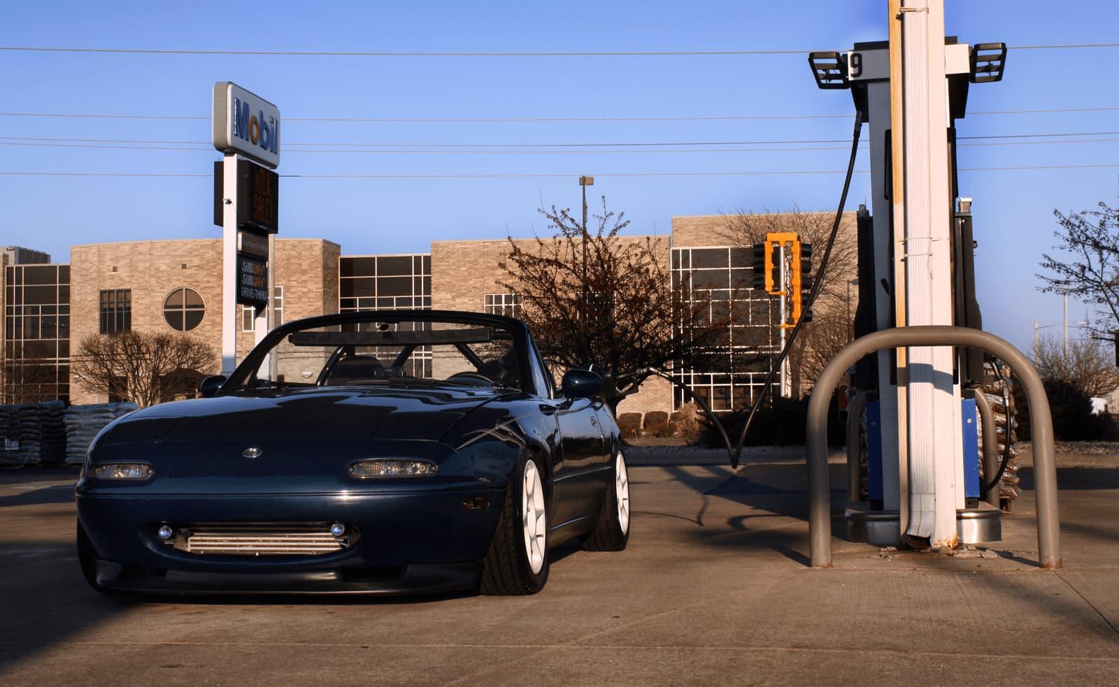 Mazda Miata filling up at the gas station