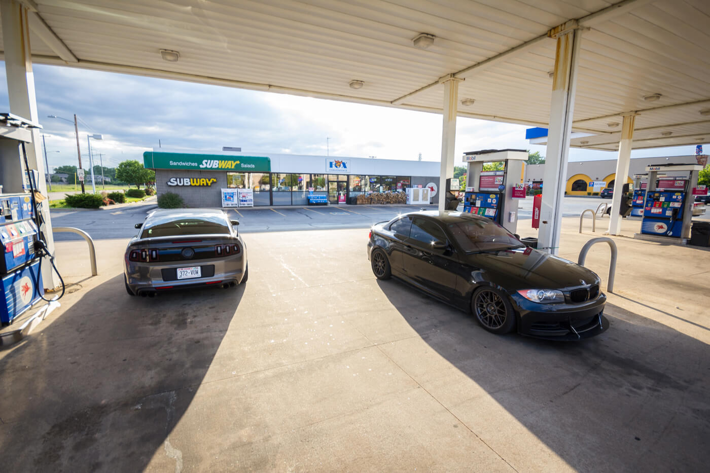 A Mustang and BMW at the gas station filling up!